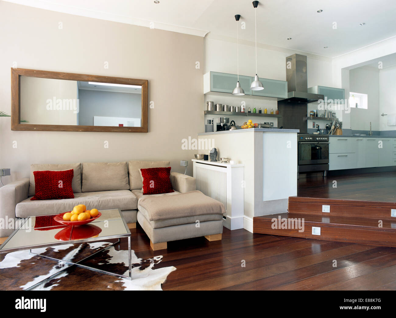 Rectangular Mirror Above Beige Suede Modular Sofa In Split Level Kitchen Living Room With Lighting Set Into Steps