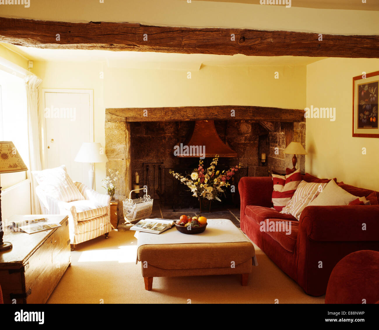 Upholstered Stool And Red Velvet Sofa In Country Living Room With Inglenook Fireplace