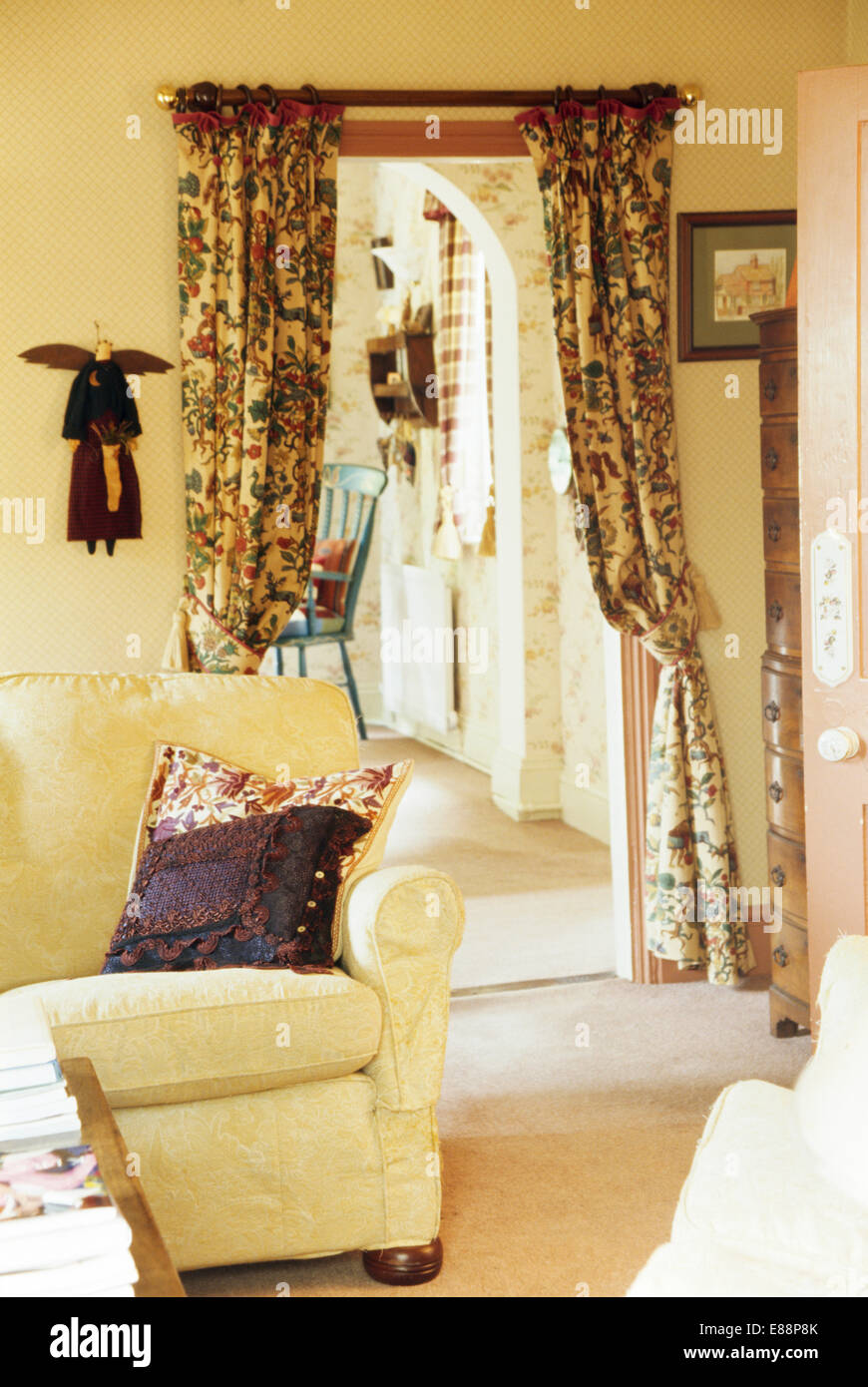 Patterned Curtains For Living Room. Cream sofa in cottage living room with patterned curtains on doorway to  small hall Stock Patterned Curtains Photos Images