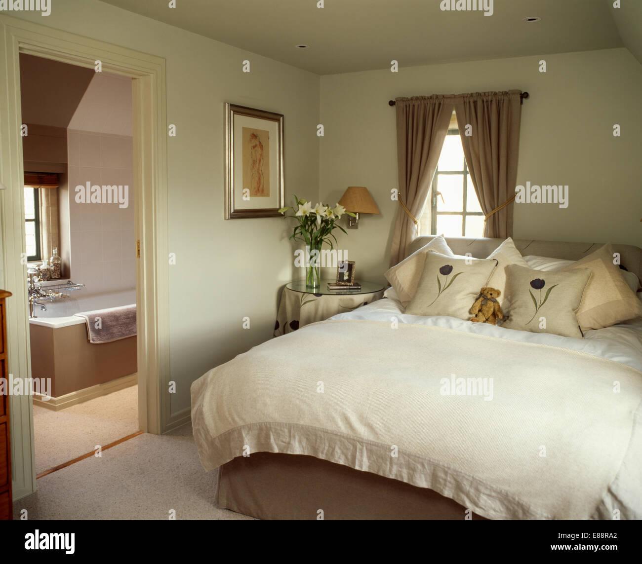 Linen edged cream fleece bed cover and cream cushions on bed in cream  bedroom with door open to ensuite bathroom. Linen edged cream fleece bed cover and cream cushions on bed in