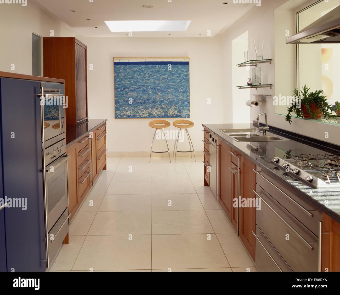 Cream travertine flooring in large modern galley kitchen with hob cream travertine flooring in large modern galley kitchen with hob set in fitted unit dailygadgetfo Images