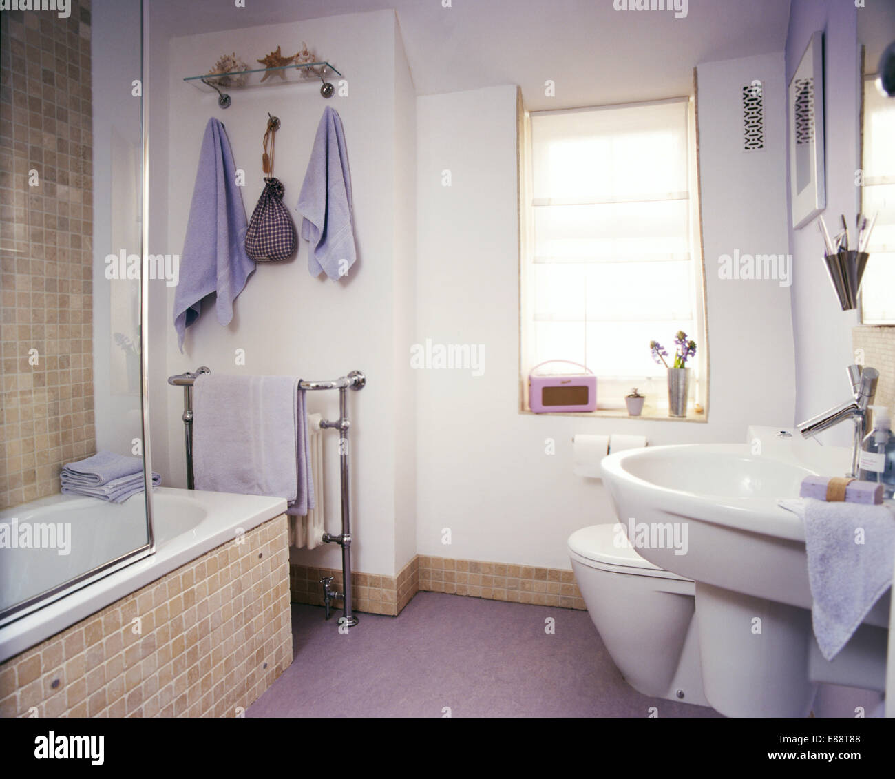 Beige mosaic tiled bath surround and skirting board in modern bathroom with  mauve towels and pink Roberts radio. Beige mosaic tiled bath surround and skirting board in modern