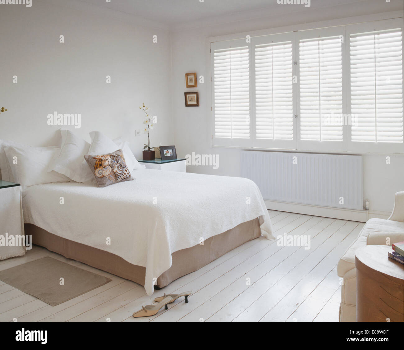 White Bedcover On Bed In White Bedroom With Plantation Shutters And White  Painted Wooden Flooring