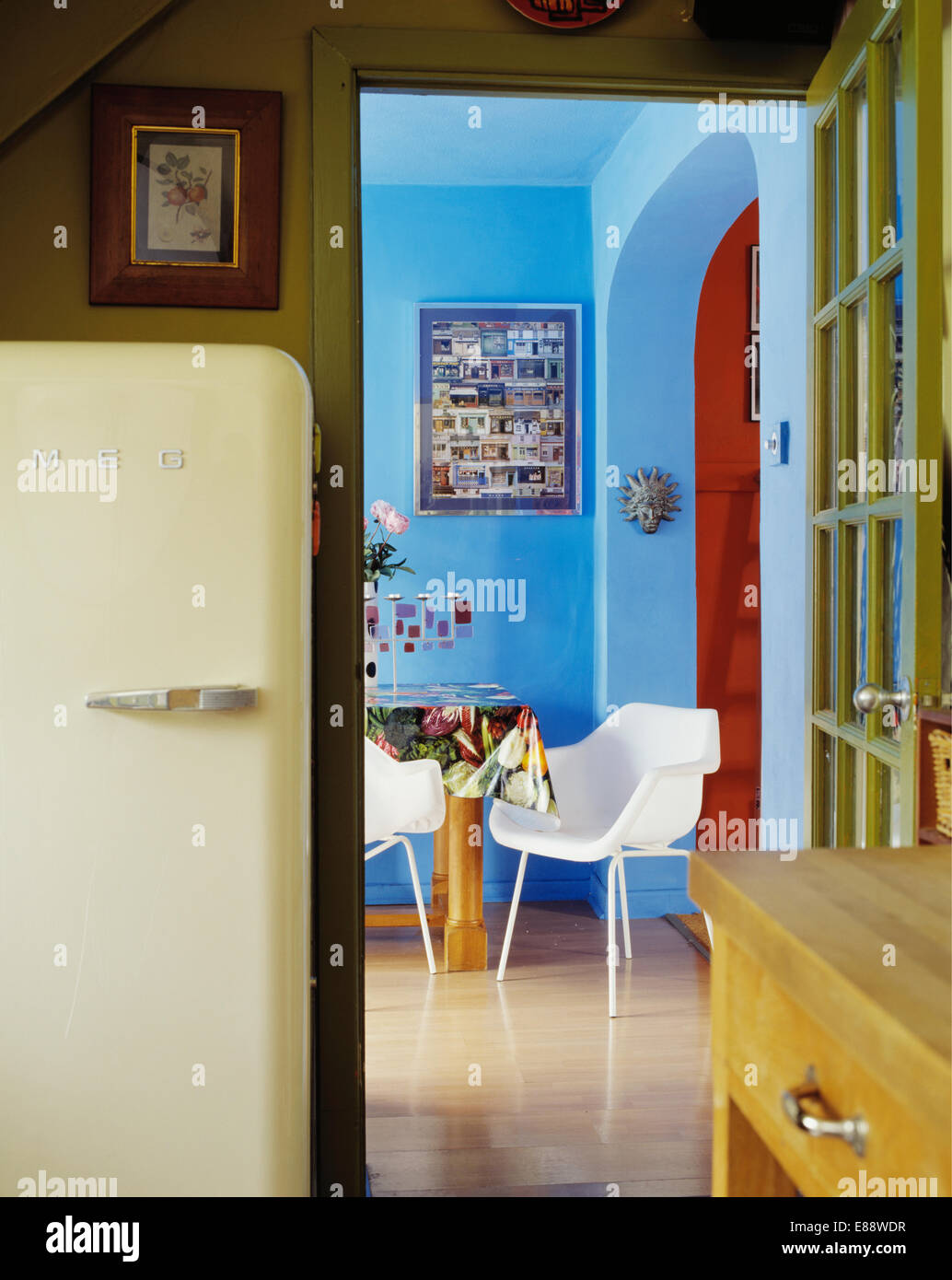 Kitchen with large cream Smeg refrigerator beside doorway to blue ...