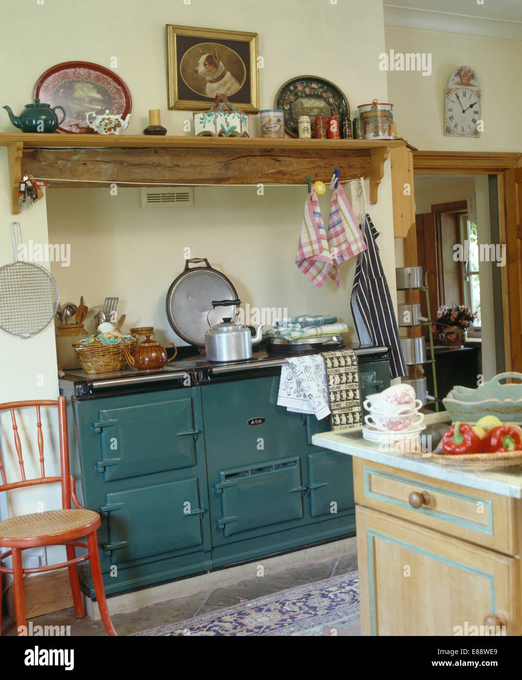 Green country kitchen - Stock Photo Wooden Shelf Above Green Aga In Traditional Country Kitchen