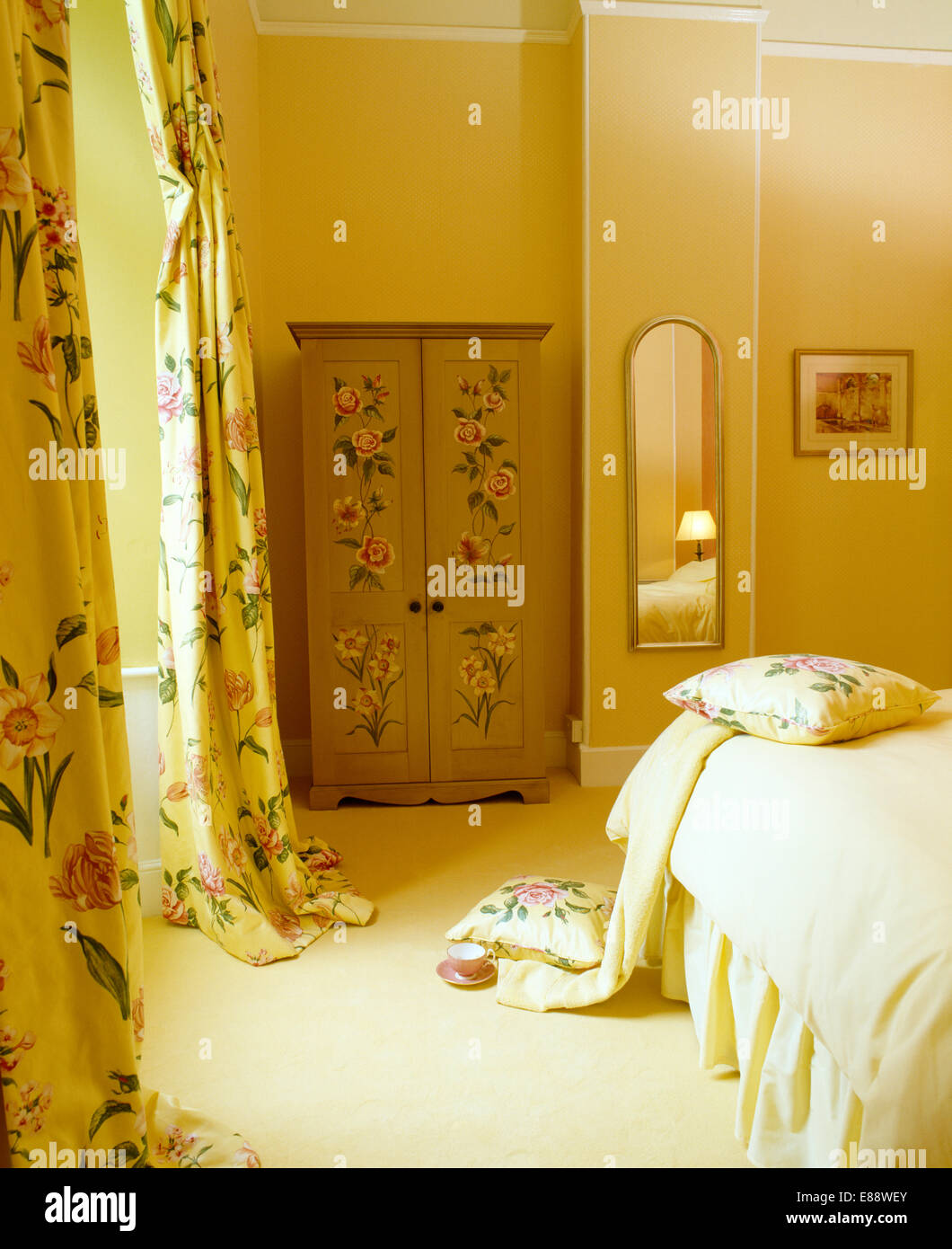 Rose-painted wardrobe in country bedroom with yellow floral silk ...