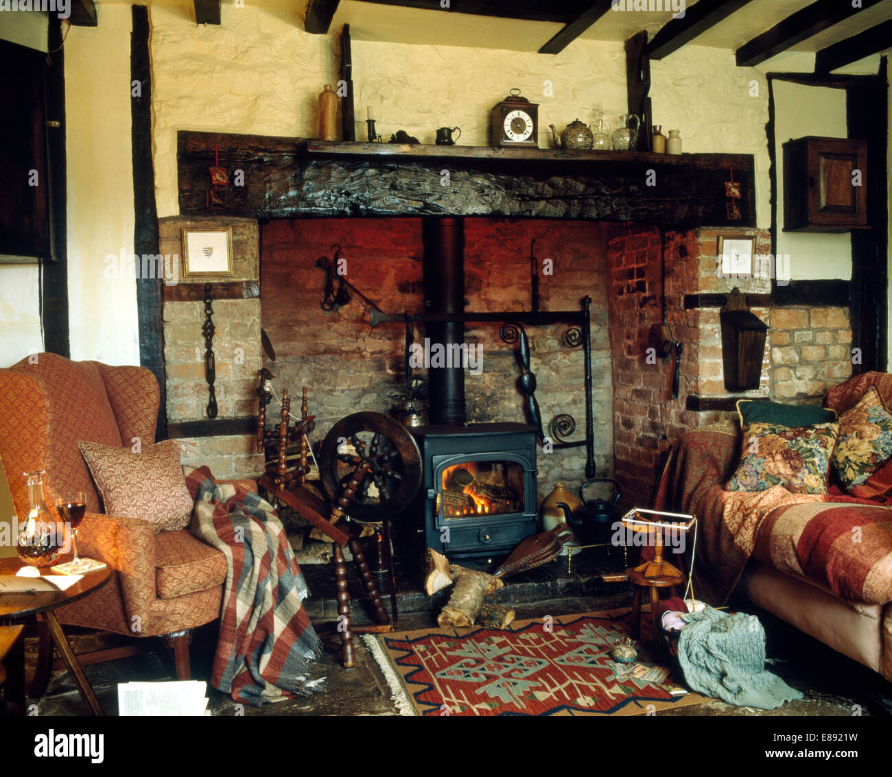 sofa and armchair piled with cushions in country living room with