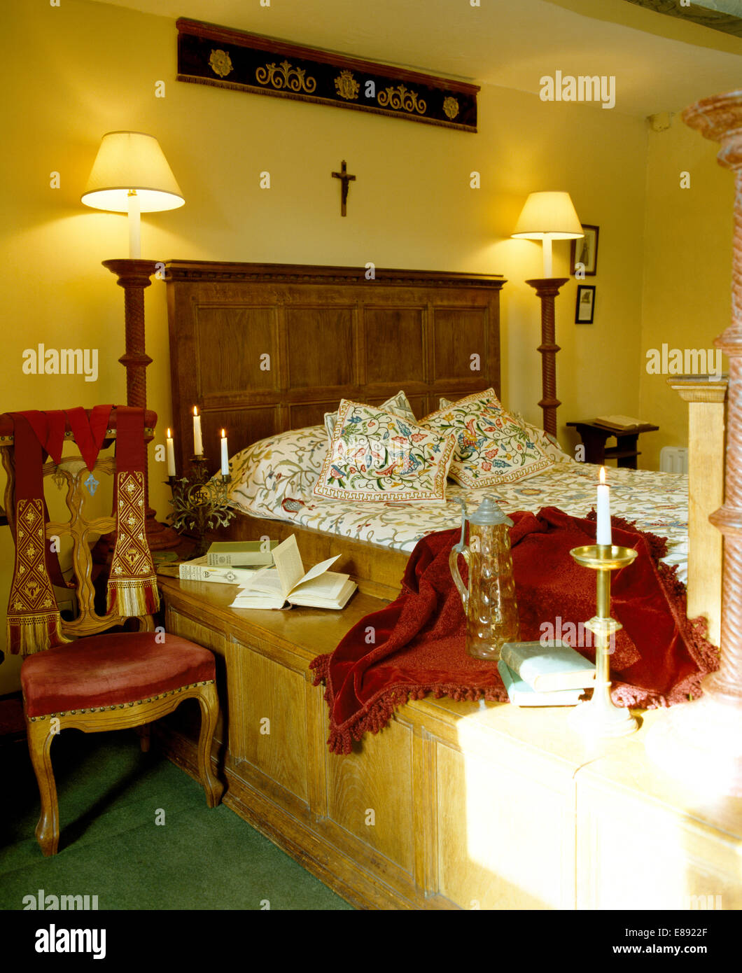 Wooden panel and crucifix on wall above wooden fitted bed and tall ...