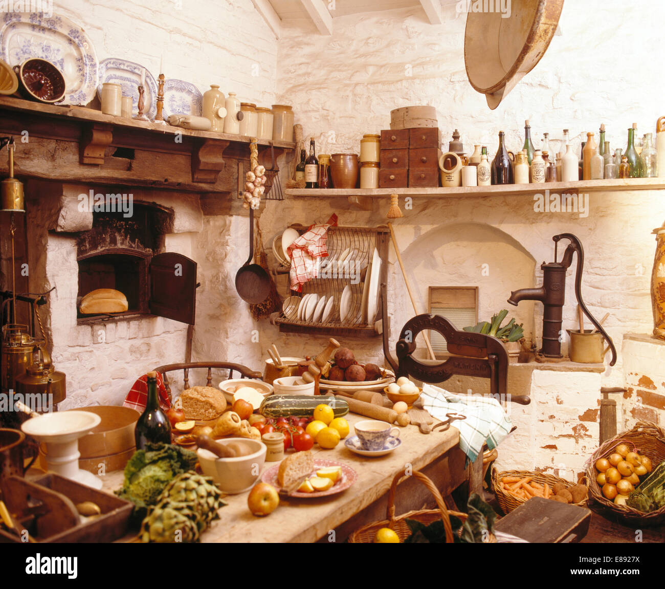 Stock Photo   Table Laden With Food In Cluttered Old Fashioned Kitchen