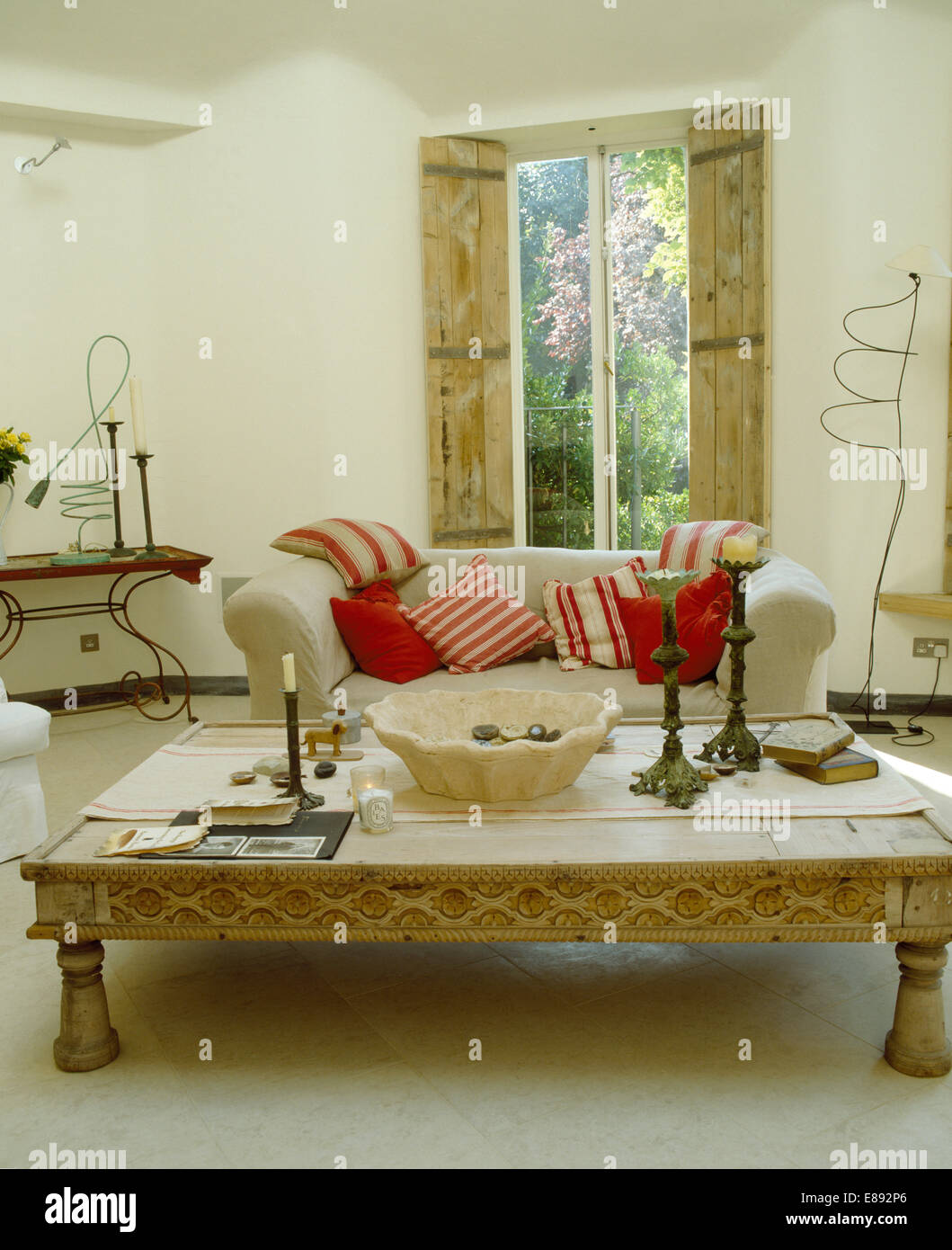 Limewashed Indonesian Coffee Table In Living Room With White Sofa With Red  Cushions In Front Of