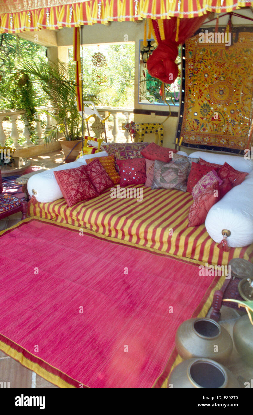 Bright Pink Rug On Floor In Front Of Sofa With White Bolsters And