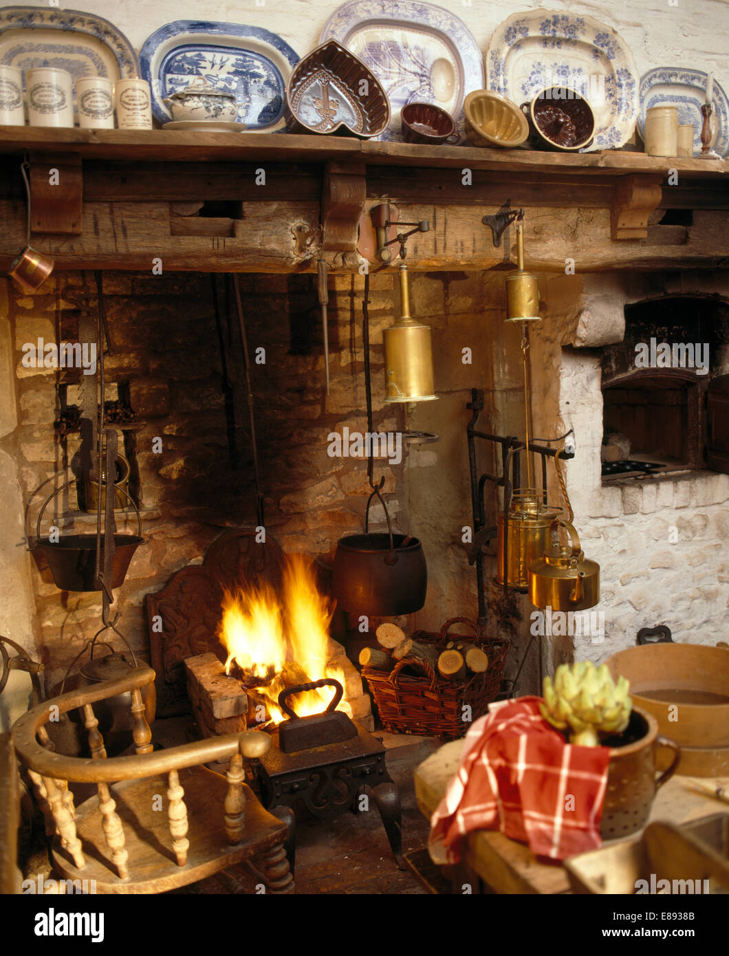 Wooden chair beside inglenook fireplace with lighted fire and row ...