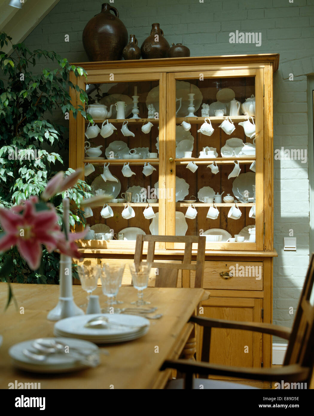 Old Pine Dresser With Collection Of White China Behind Glass Doors In Pale Green Dining Room