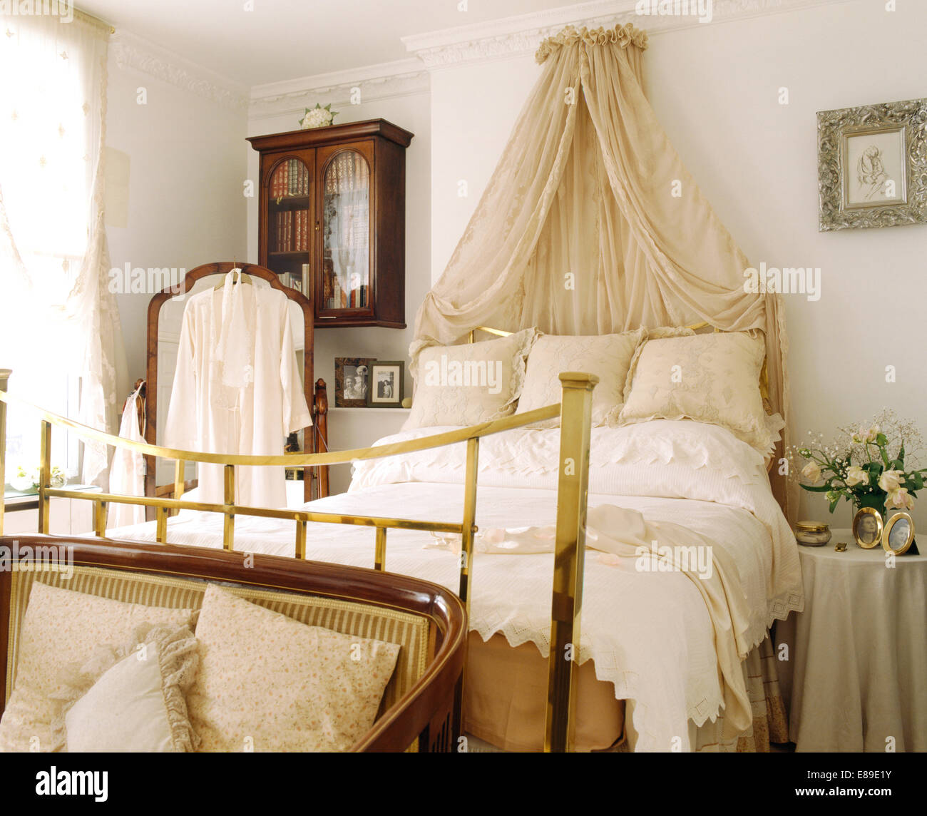 Coronet with cream voile drapes above brass bed with cream cushions and white duvet in white bedroom & Coronet with cream voile drapes above brass bed with cream ...