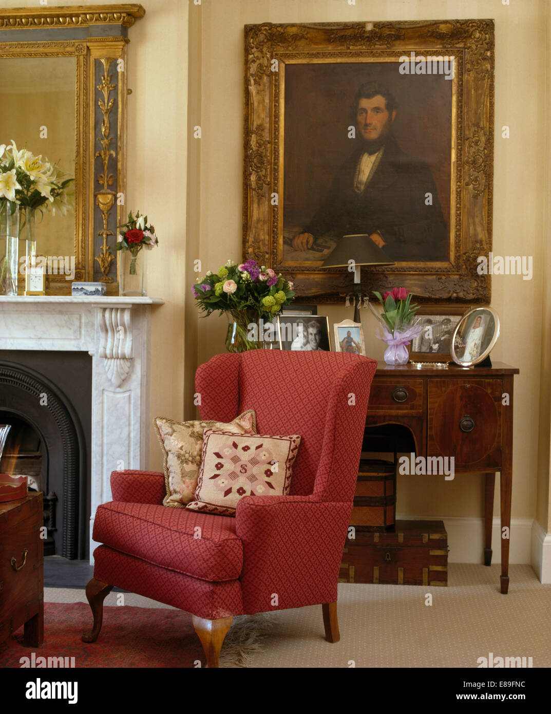 red armchair beside fireplace in drawing room with large oil