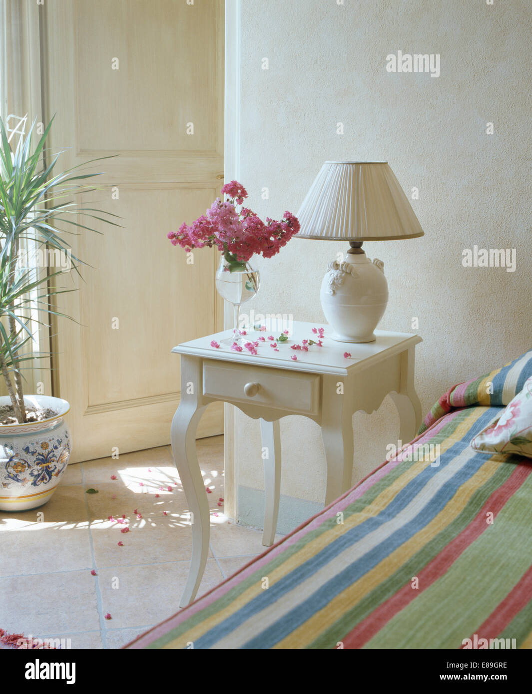 White lamp on bedside table with vase of pink flowers in bedroom white lamp on bedside table with vase of pink flowers in bedroom with colourful striped cover on the bed aloadofball Choice Image