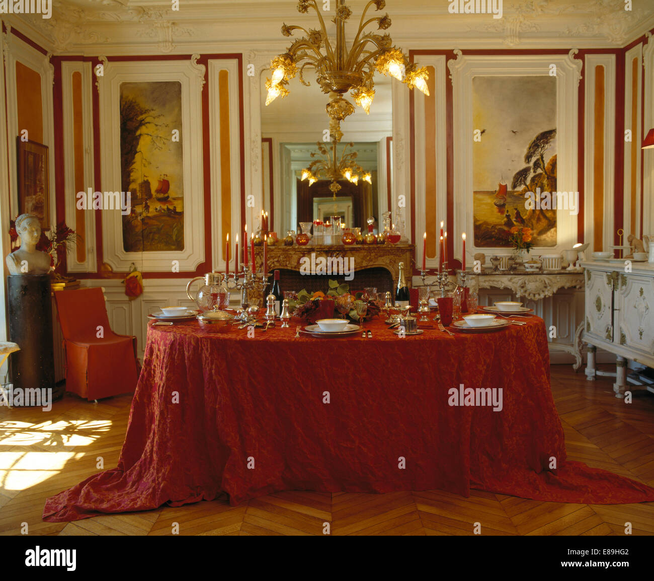 chandelier above table set for dinner with rich red cloth in chandelier above table set for dinner with rich red cloth in french apartment dining room with painted murals