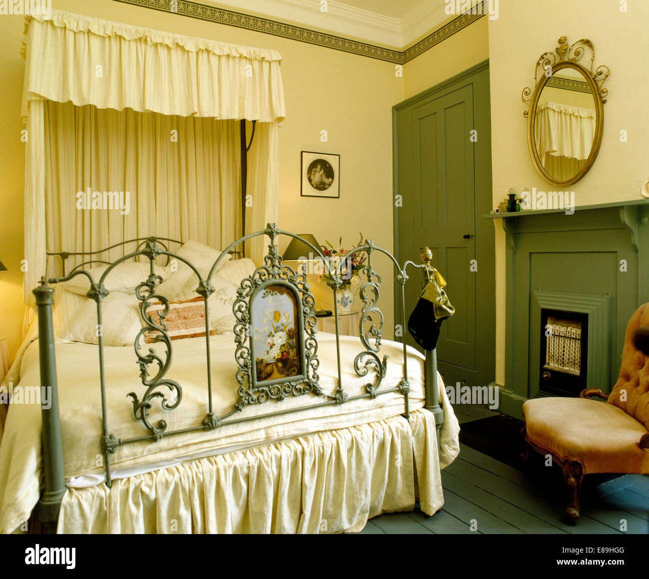 Cream drapes and canopy of ornate antique half-tester bed in bedroom with old gas fire in green fireplace & Cream drapes and canopy of ornate antique half-tester bed in ...