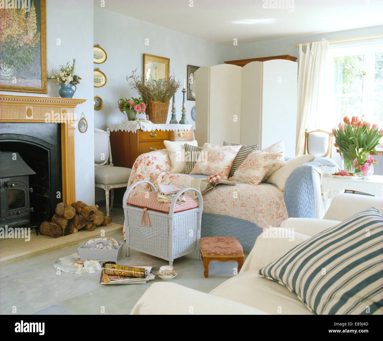 Quilted Cushions And Throws On Sofa Beside Fireplace With Wood Burning Stove In Cottage Living Room