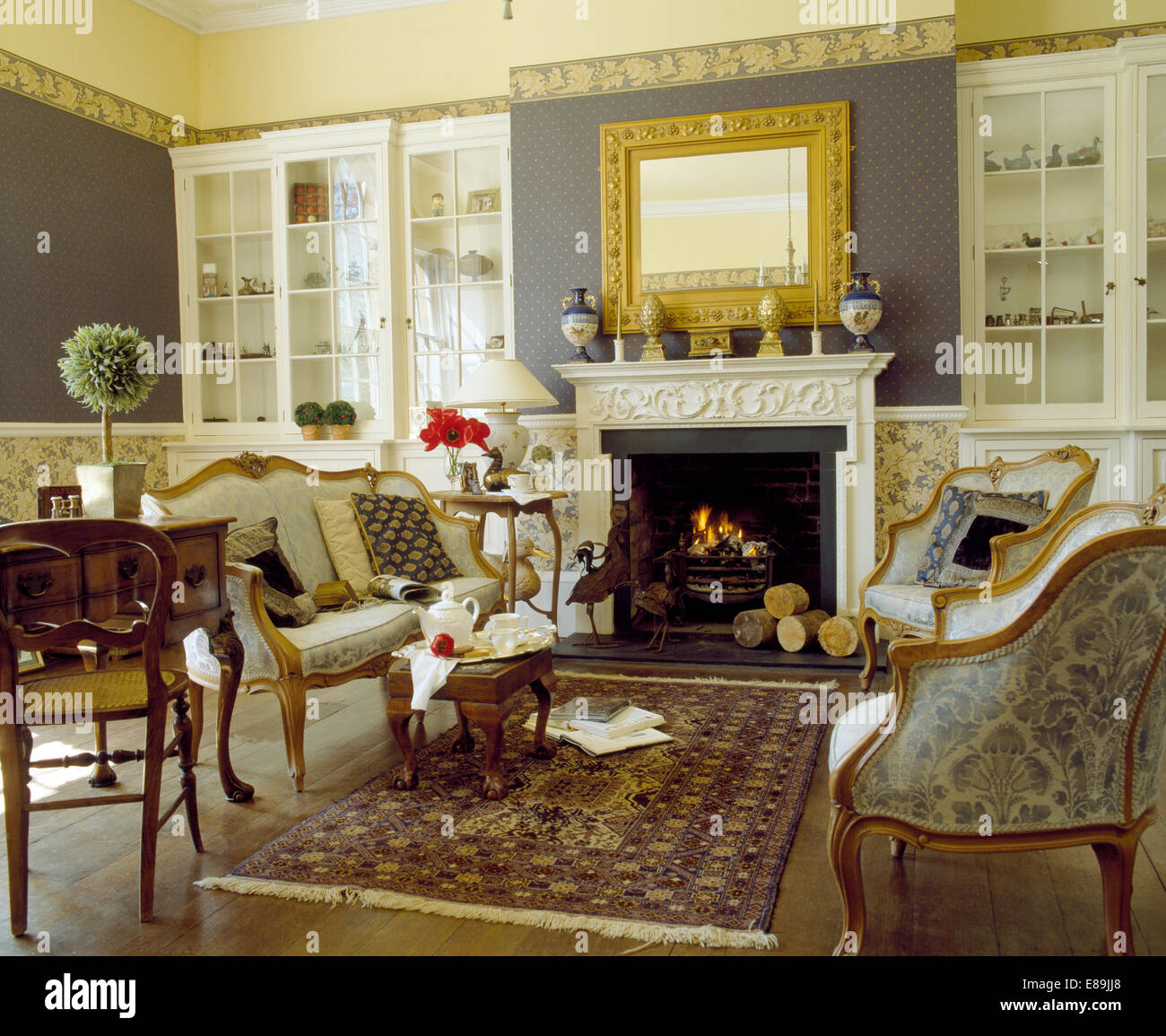 Muted Oriental Rug And French Sofa And Armchairs In Country Living Room  With Bookcases On Either Side Of Fireplace