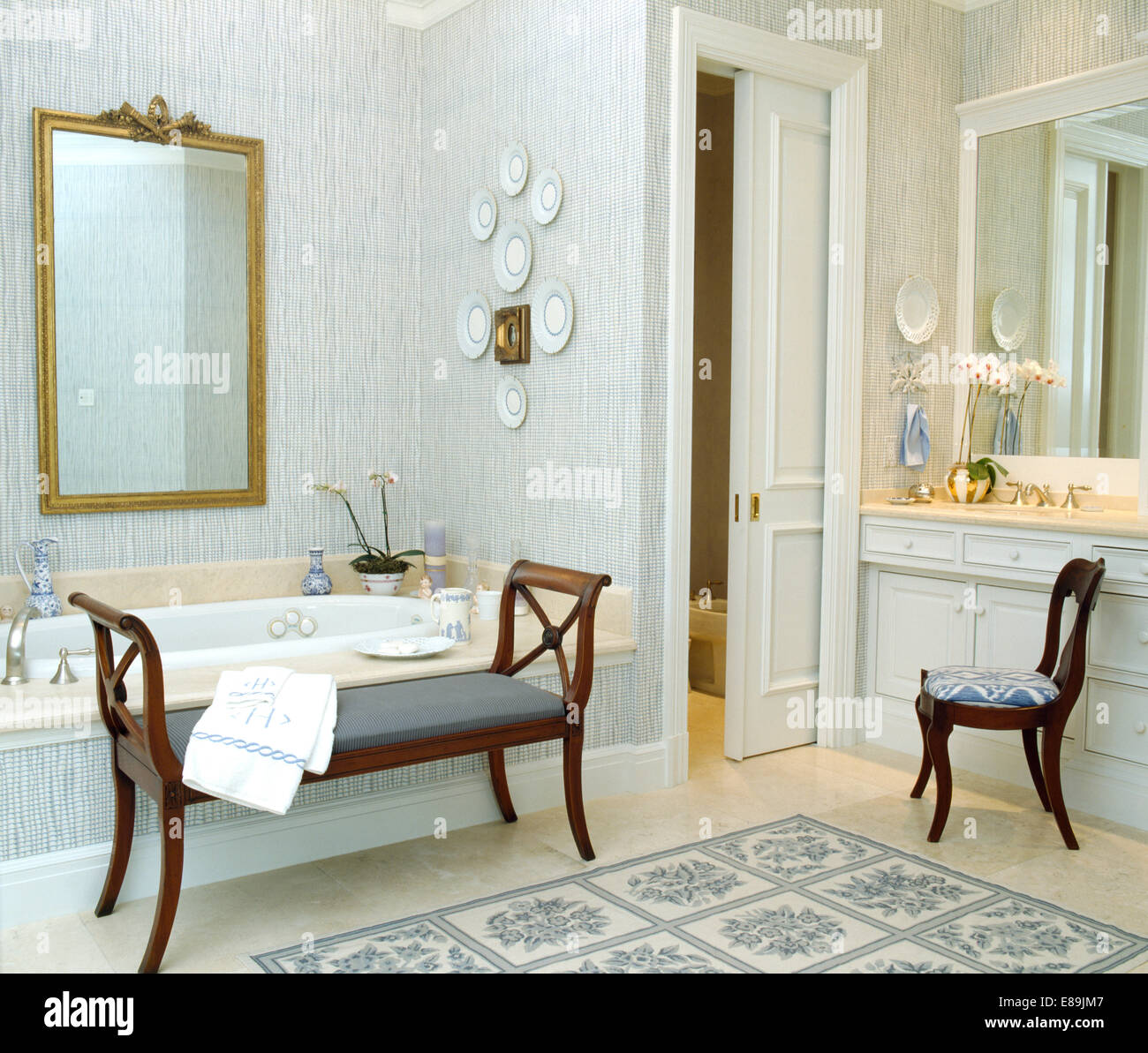 Blue Wallpaper And Large Gilt Mirror In Traditional Bathroom With Sliding  Door And Antique Stool And Chair