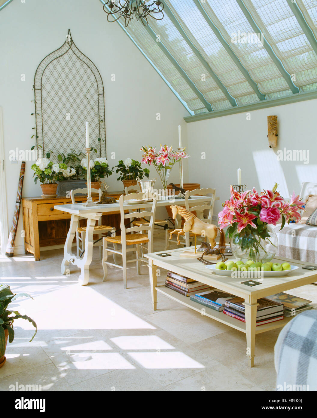 Vase of pink lilies on coffee table in conservatory living and vase of pink lilies on coffee table in conservatory living and dining room with travertine floor and metal ogee trellis on wall geotapseo Image collections