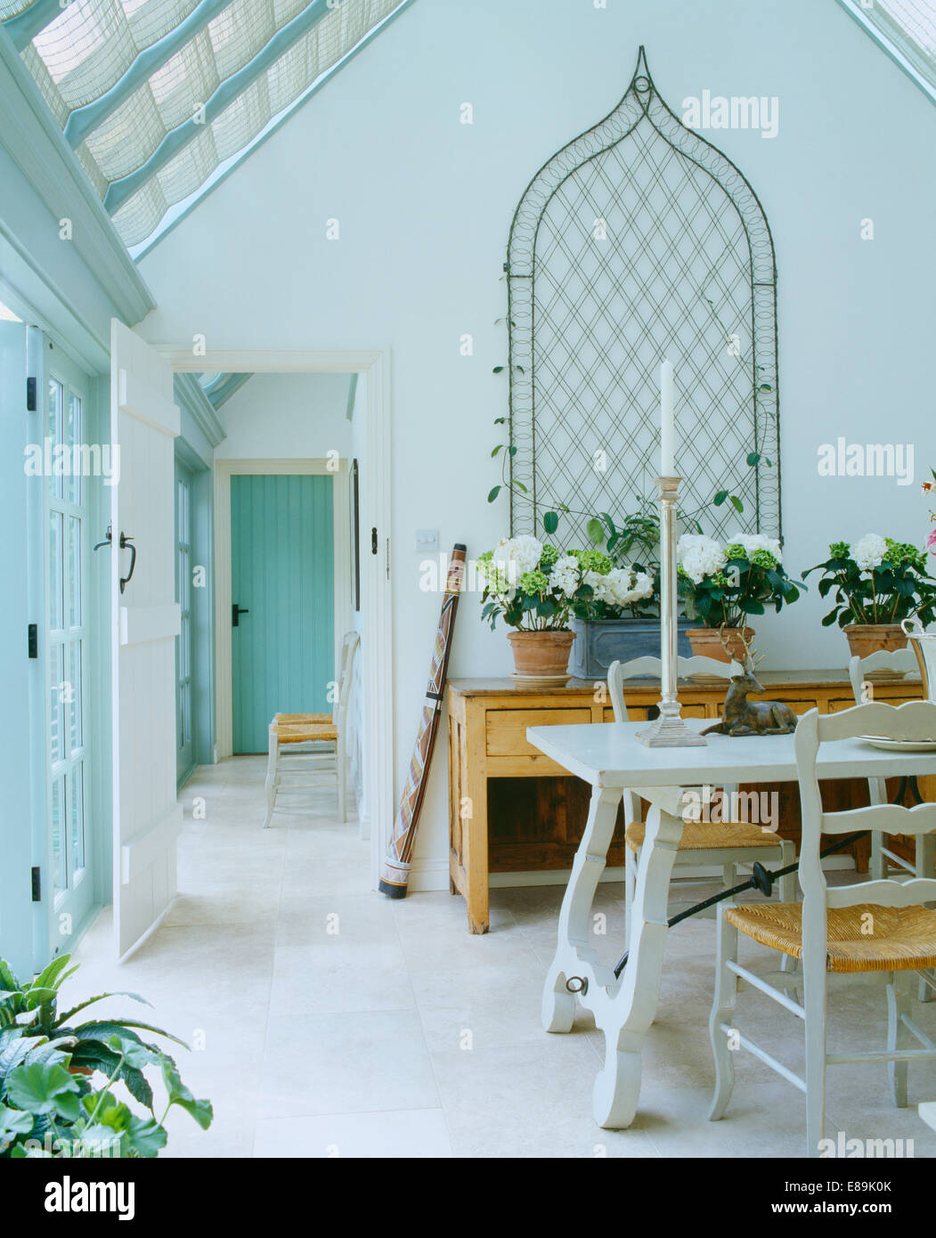 Metal Ogee Trellis On Wall Above Sideboard In White Conservatory Dining Room With Travertine Flooring