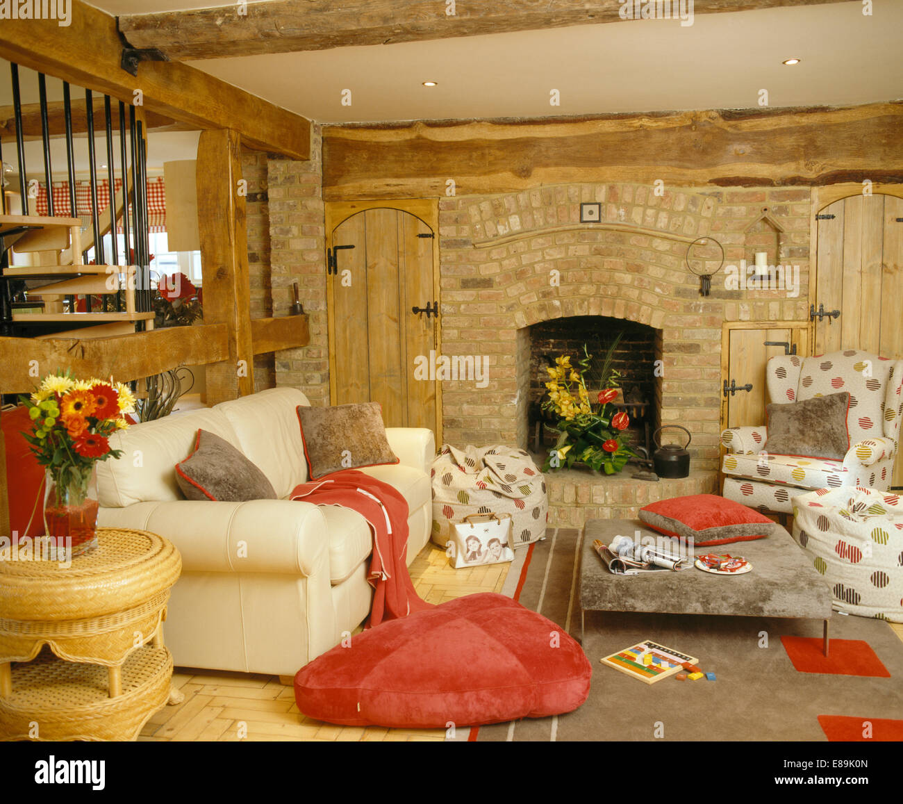 Red Floor Cushion Beside Cream Sofa In Country Living Room With Fireplace Exposed Brick Wall