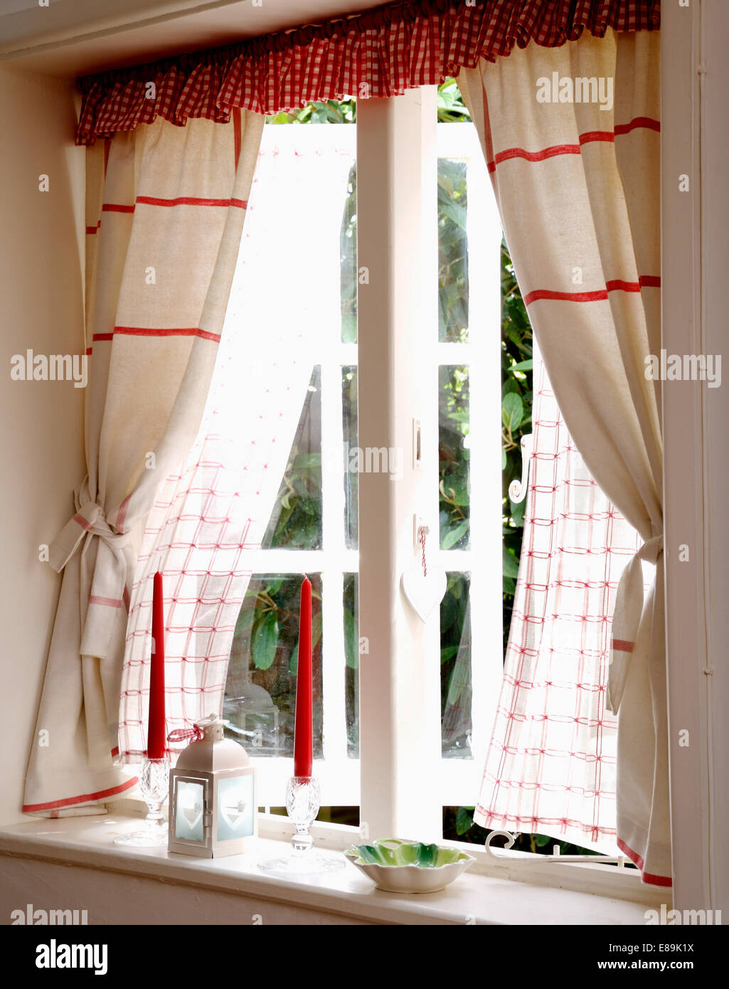 Red striped white linen curtains with red checked pelmet at open ...