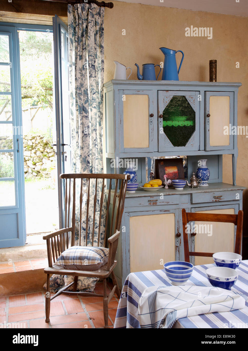 Blue White Fifties Dresser In Country Kitchen Dining Room With Wooden Chair Front Of French Doors