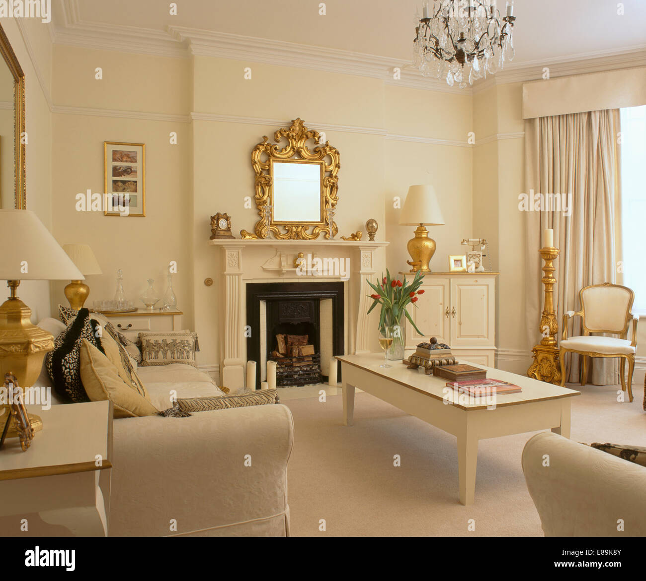 Cream living room with cream table and sofas and gold accessories stock photo royalty free Gold accessories for living room