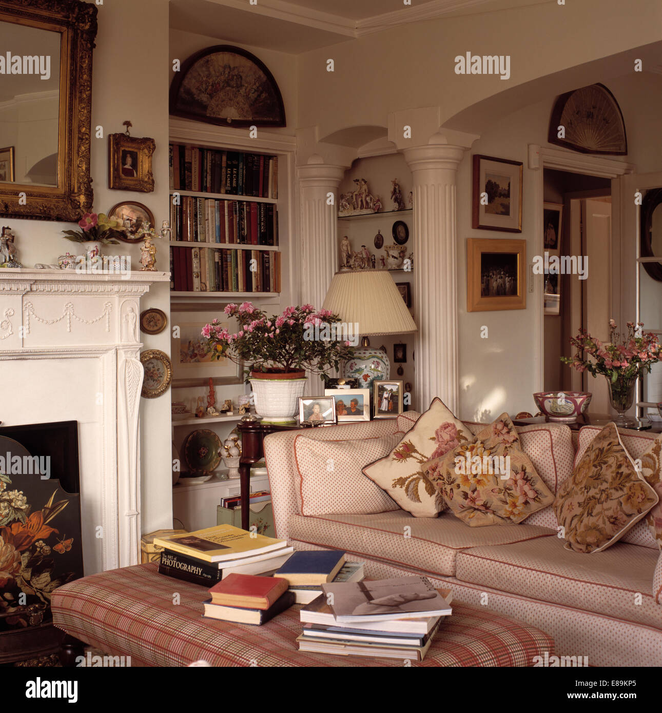 Stock Photo   Tapestry Cushions On Cream Sofa In Country Living Room With  White Fluted Pillows And Upholstered Stool With Pile Of Books
