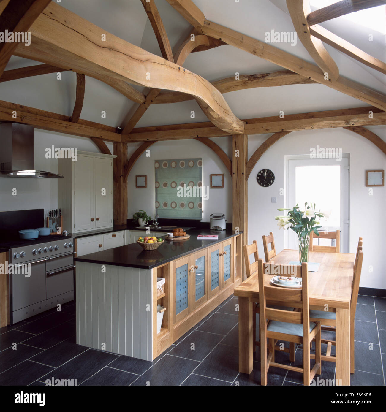 Large Wooden Beams And Island Unit In Barn Conversion Kitchen With Pale  Wood Table And Chairs