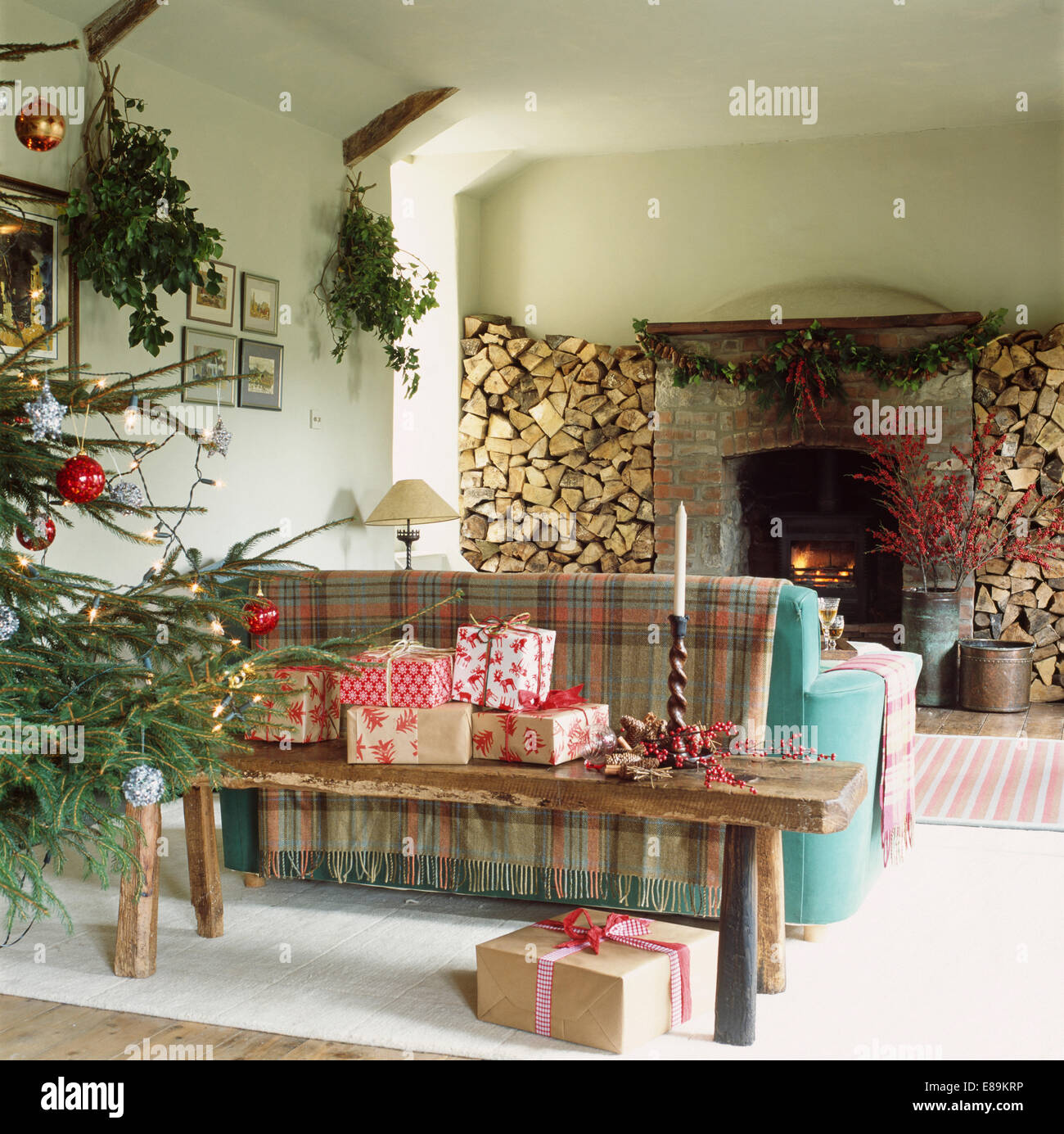 Christmas Presents On Rustic Wooden Bench Behind Sofa In Living Room With Logs Stored Either