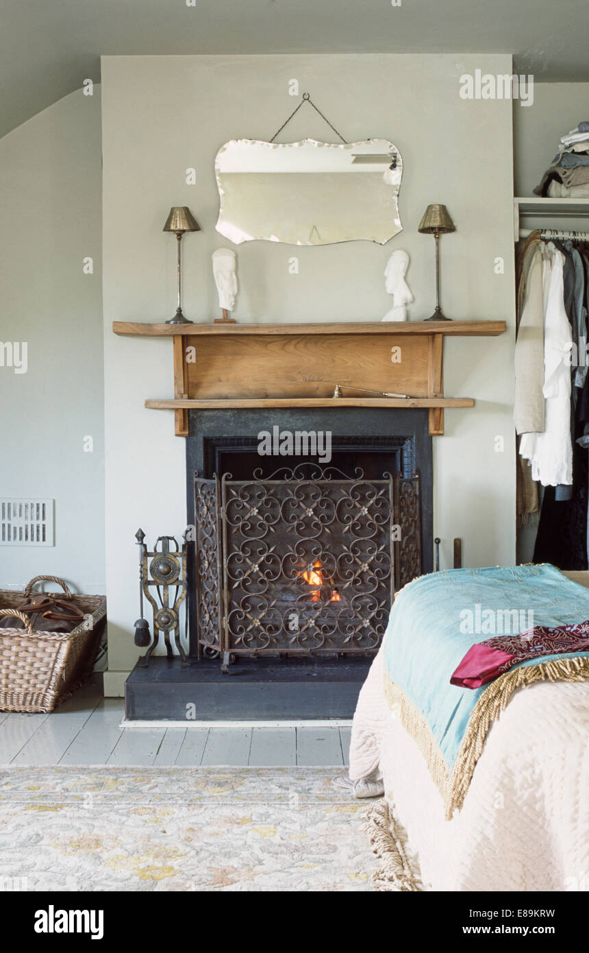 thirties mirror above fireplace with wrought iron fireguard in