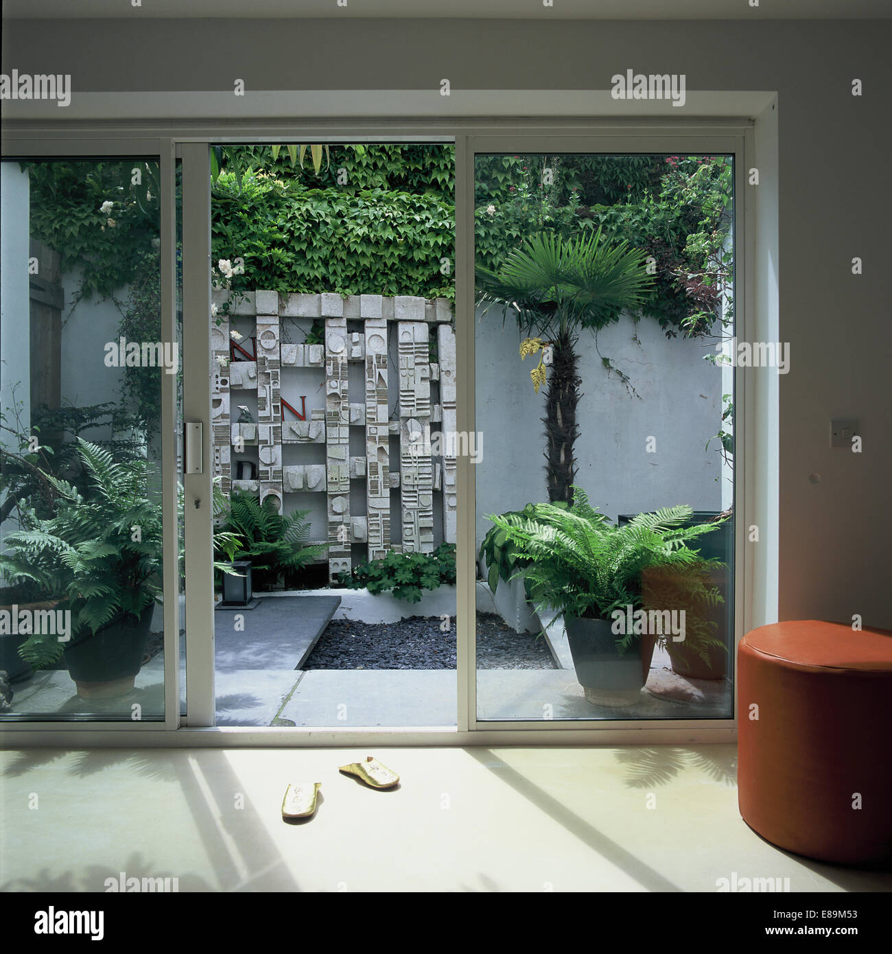 Stock photo view through glass patio doors to courtyard garden with wall sculpture