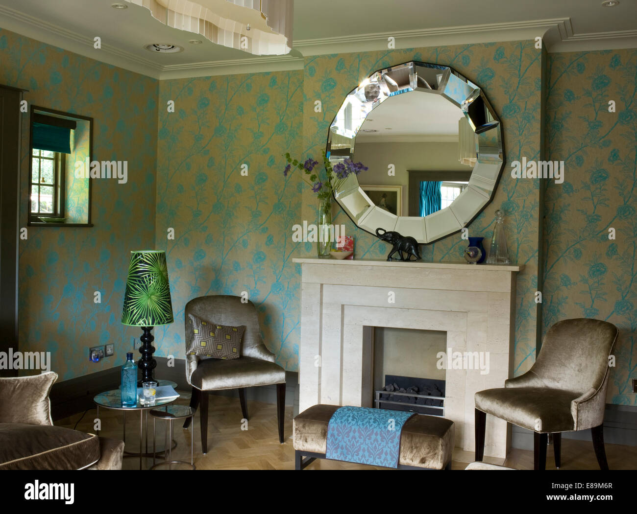Round mirror above fireplace in traditional sitting room with grey ...