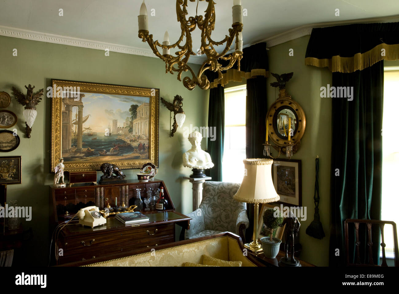 Large oil painting above antique bureau in green drawing room