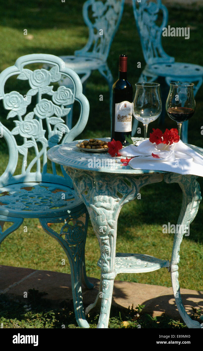 White metal garden chairs - Close Up Of Ornate White Metal Garden Chair And Table With Glasses And Bottle Of Red Wine