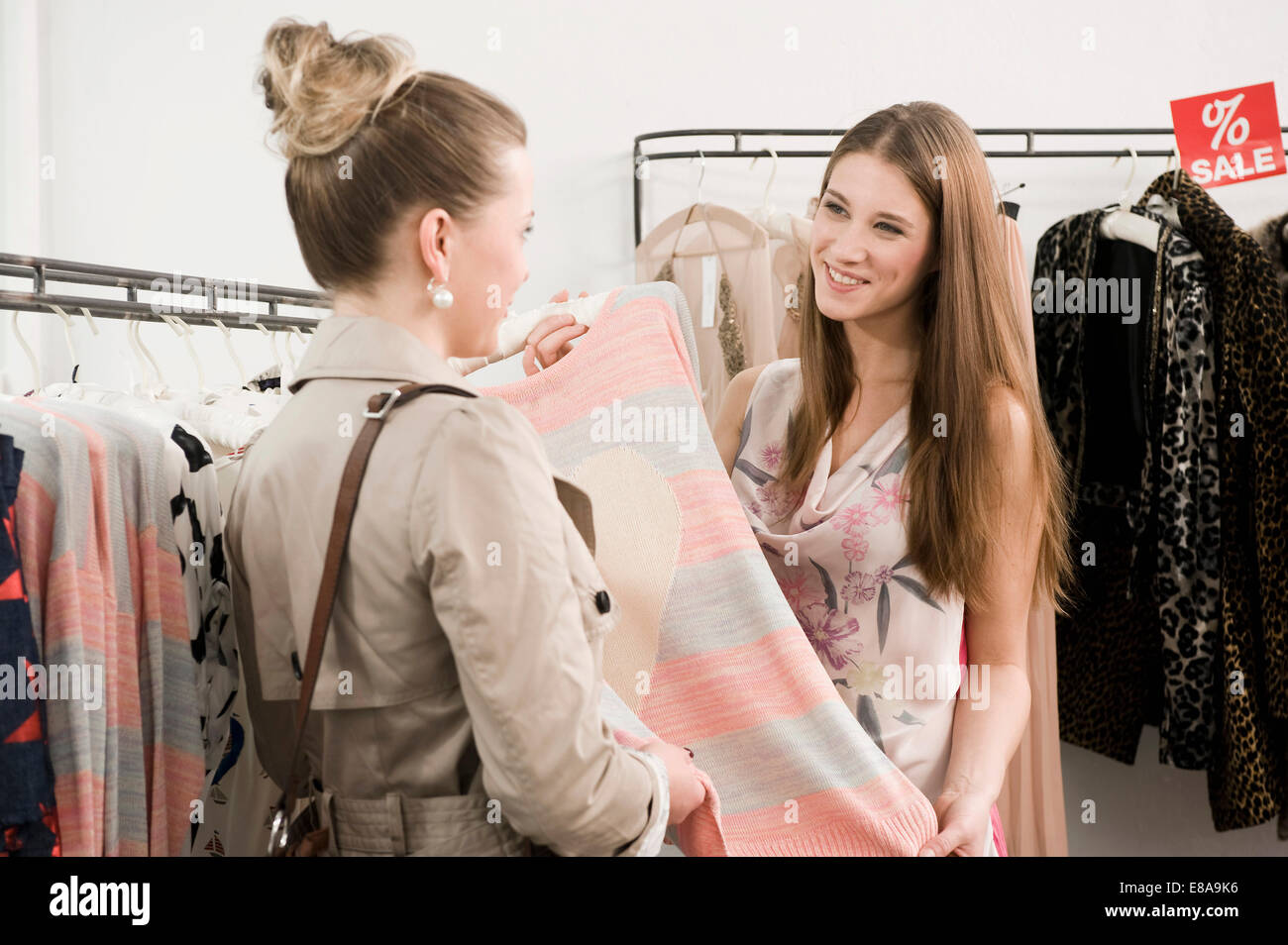 clothes shop assistant store stock photos clothes shop assistant s girl customer in fashion store stock image