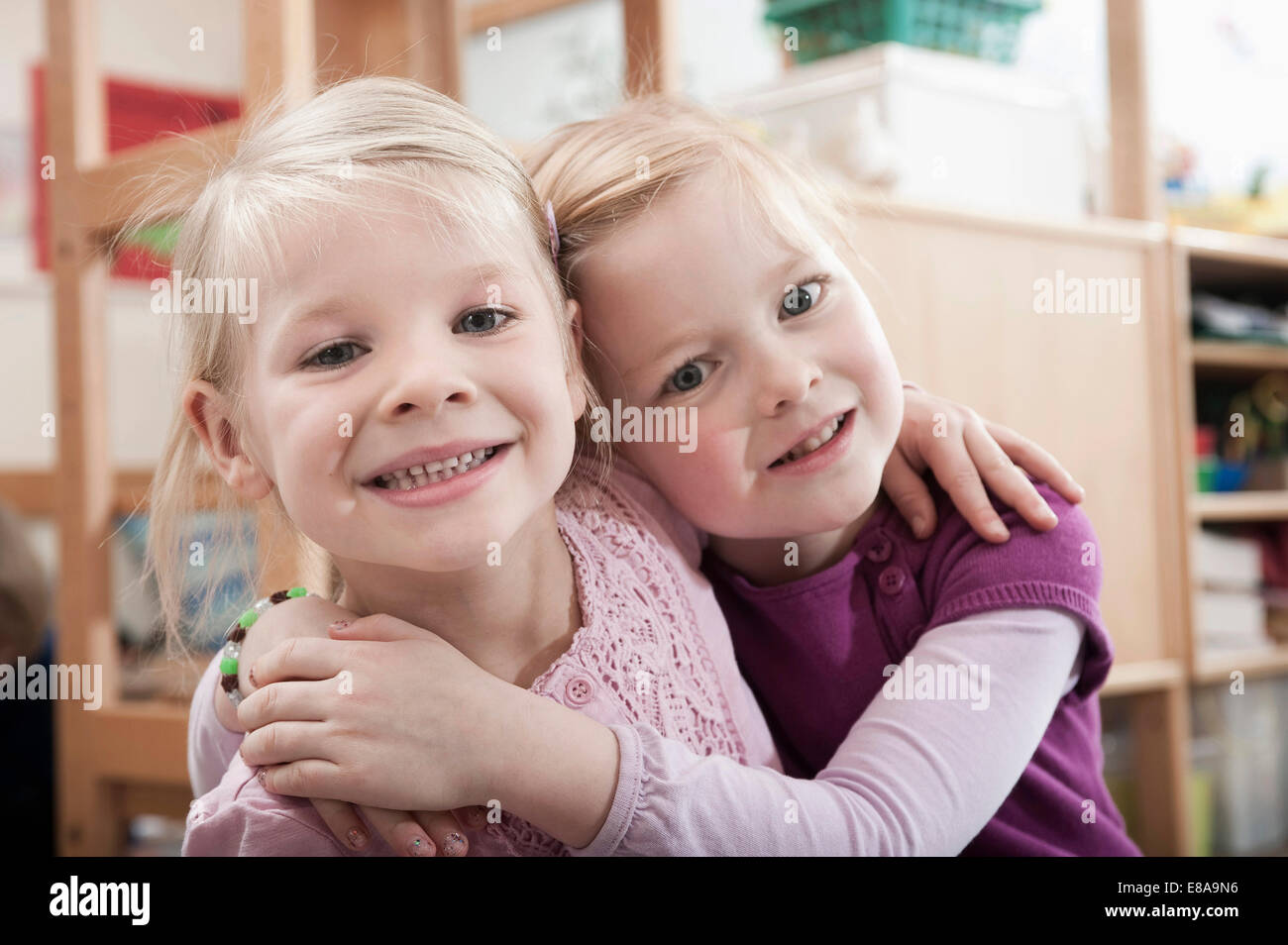 kindergarten girl side Portrait of two little girls, best friends, side by side in kindergarten -  Stock
