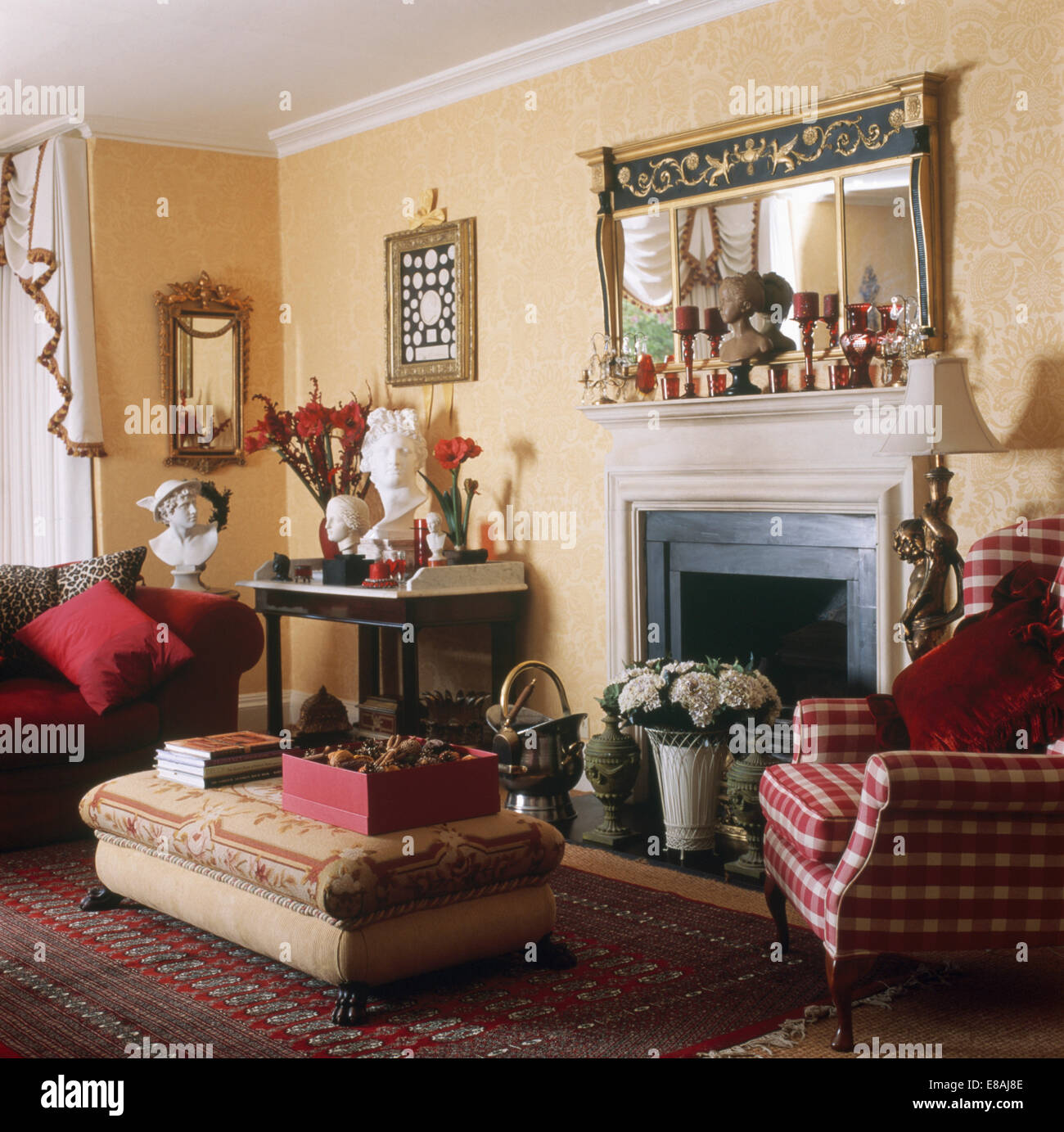 ottoman and red checked armchair beside fireplace with pot of white hydrangeas in traditional living room