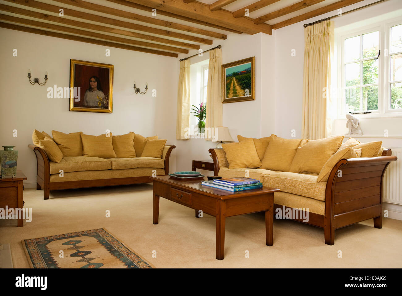 Ochre Yellow Cushions On Mahogany Framed Sofas In Cream Country Living Room  With Beamed Ceiling And Cream Carpet Part 64