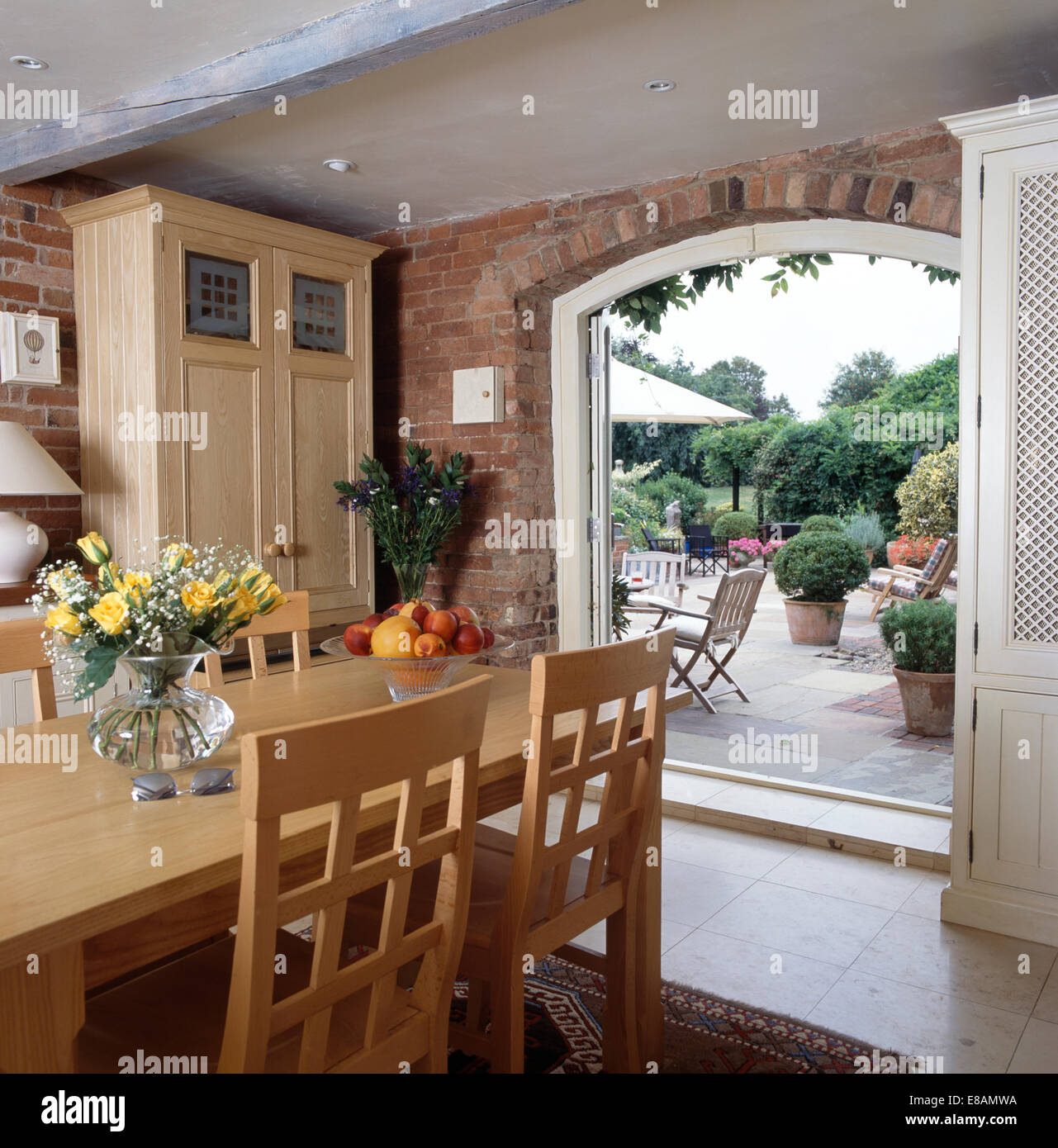 Pale Wood Dining Table And Chairs In Room With Double Doors Open To Large Patio