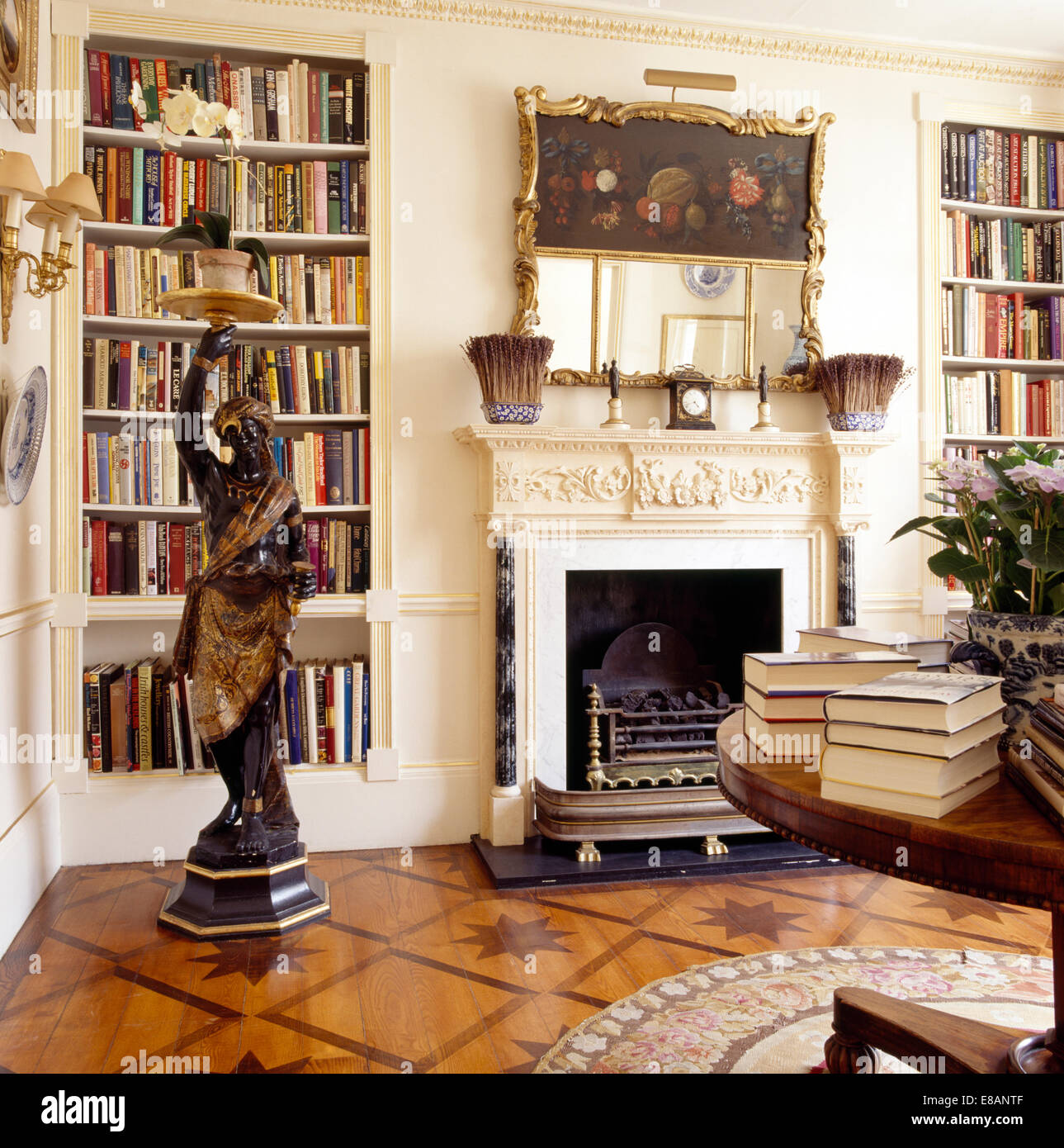 Blackamoor statue in living room with alcove bookshelves on either ...