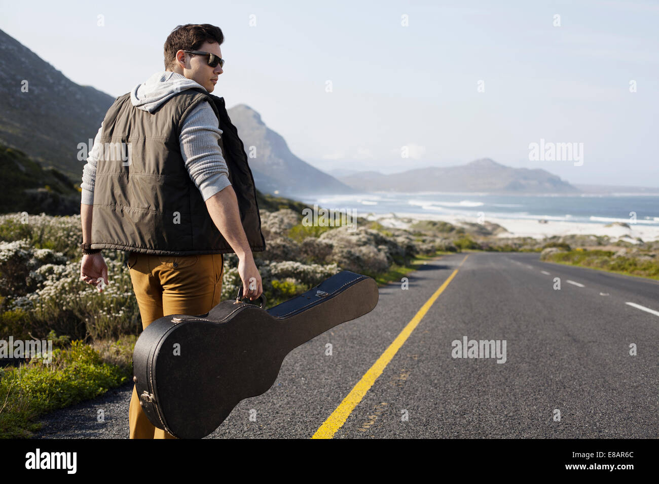 Rear View Of Young Man Walking On Coastal Road Carrying Guitar Case Cape Town Western South Africa