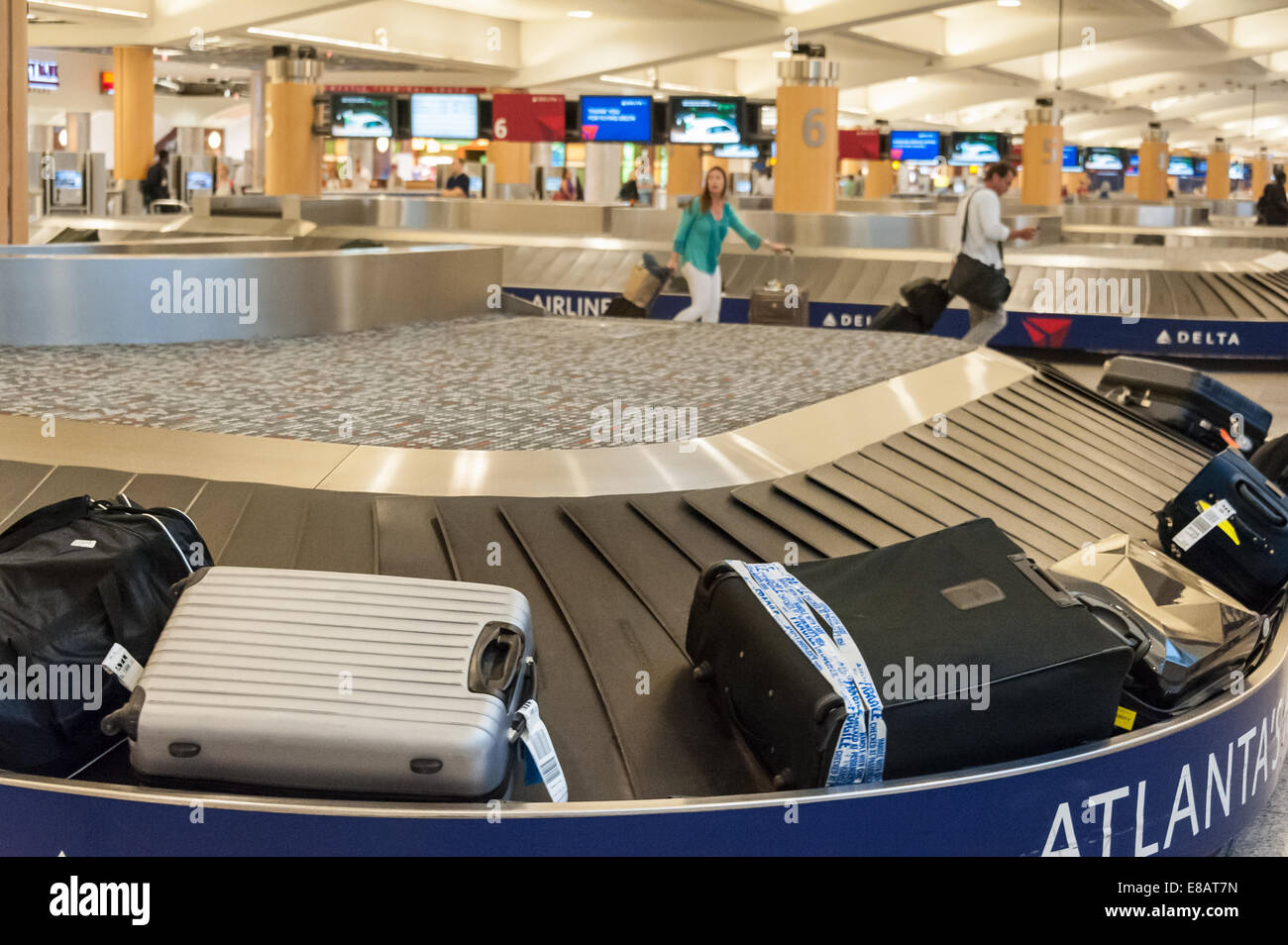 baggage claim carousel and airline passengers at