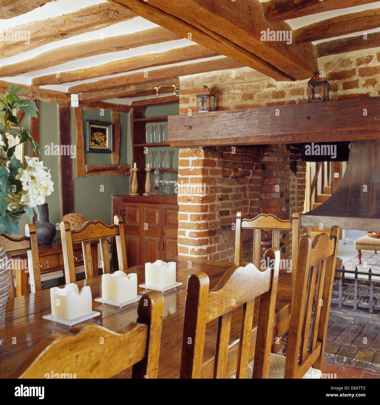 Wooden Chairs And Table In Beamed Cottage Dining Room With Open Fireplace