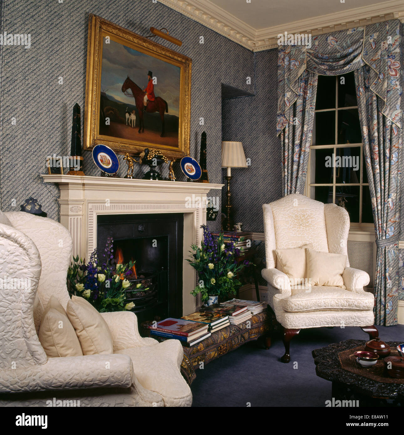 cream wing chairs on either side of fireplace in traditional stock