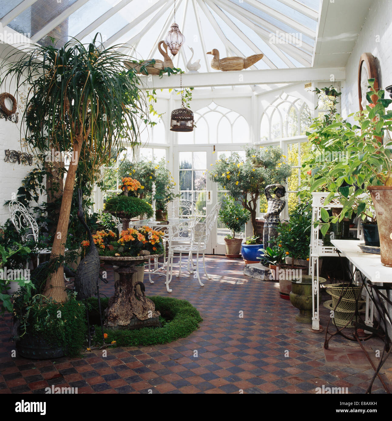 Old blackterracotta tiles on floor of conservatory dining room old blackterracotta tiles on floor of conservatory dining room with lush green houseplants and helxine edged a stone urn dailygadgetfo Choice Image